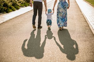 Family walking with baby. image of family's shadows